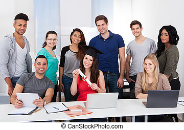 University Student Holding Degree In Classroom - Portrait of...