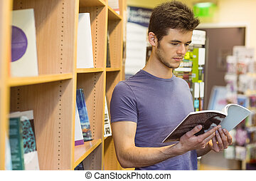 University student standing reading textbook in the bookcase...
