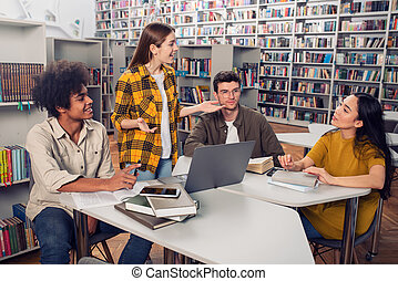 University students are studying in a library together. Concept of teamwork and preparation