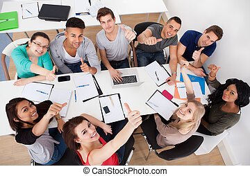 High angle view of university students doing group study at desk in classroom