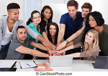 University Students Stacking Hands At Desk
