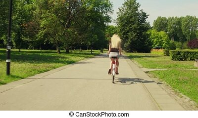 Unknown blonde woman cycling along park road