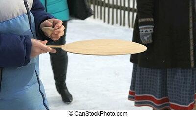 Unknown boy rotates wooden spinner. Close-up - Unknown boy...