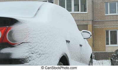 Unknown car covered with snow in the yard in winter season