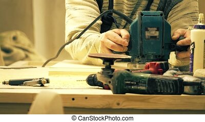 Unknown carpenter sawing wooden board with a portable jigsaw...