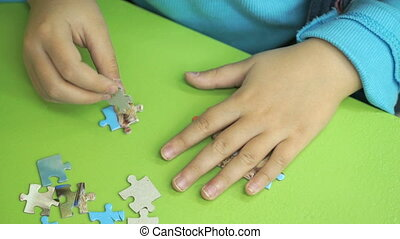 Unknown child collecting puzzles at the table - Close-up of...