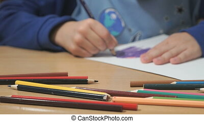 Unknown child drawing pictures. Close-up - Close-up of hands...