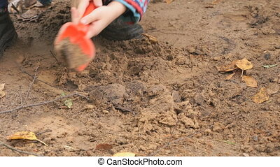 Unknown child playing with sand in sandbox