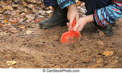 Unknown child playing with sand in sandbox - Hands of...