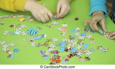 Unknown children collecting puzzles at the table - Close-up...