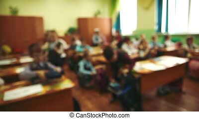 unknown children sit in school in the classroom at their...