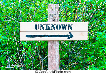 UNKNOWN written on Directional wooden sign with arrow pointing to the right against green leaves background. Concept image with available copy space