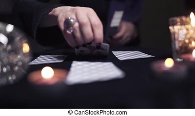 Unknown female witch with black manicure is handing out fortune telling cards while sitting at a dark table in the room. The concept of dark forces and belief in occult powers. Sinful concept