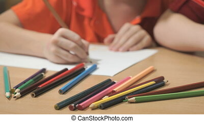Unknown little boy drawing pictures. Close-up - Close-up of...