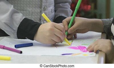 Unknown little boy paints pictures with felt-tip