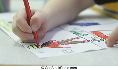 Unknown little child paints pictures with felt-tip -...