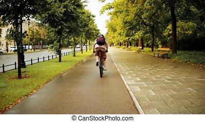 Unknown man cycling along urban bike path after summer rain
