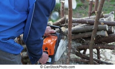 unknown man logger sawing trees with chainsaw in the forest