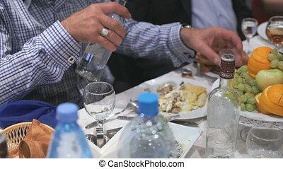 Unknown man pour vodka in glass - Wedding feast -...