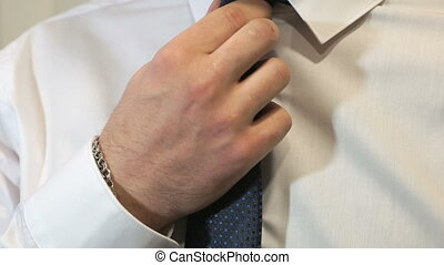 Unknown man tightening tie in front of camera - Unknown...