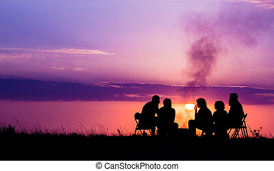 unknown people sitting near campfire against sunset with...