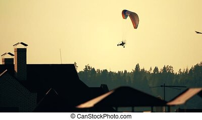 Unknown powered paraglider flying above the forest and town rooftops at sunset. Slow motion shot