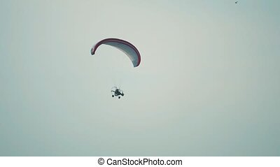 Unknown powered paraglider flying against blue sky