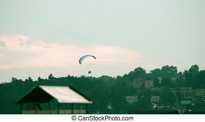 Unknown powered paraglider flying near the town - Unknown...