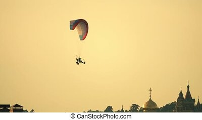 Unknown powered paraglider flying against ancient Russian monastery at sunset
