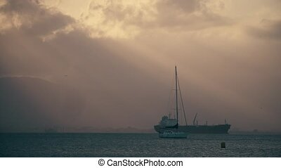 Unknown sailboat and cargo ship at sea in the evening -...