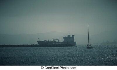 Unknown sailboat and cargo ship at sea near Gibraltar -...