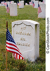 The grave of an unknown US soldier marked with a flag on Memorial Day in a military cemetery.