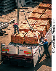 unlading bricks in construction site