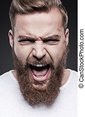 Unleashed emotions. Portrait of furious young bearded man shouting while standing against grey background
