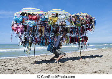 street vendor on a beach - unlicensed street vendor on a...