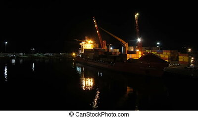 Unloading Cargo from a Ship in the Sea Port of Batumi by Night. Time Lapse