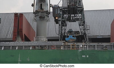 Unloading cargo ship. - Crane with bucket unloads raw and...