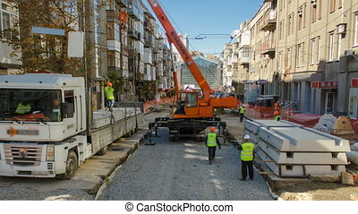 Unloading concrete plates from truck by crane at road...