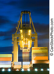 Huge crane unloading containers from a container ship at dusk