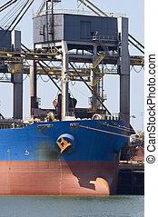 Unloading iron ore - A huge crane unloading ore from a bulk...
