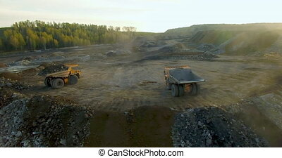 Unloading land and stones from quarry dump trucks. Aerial view drone flies to the left