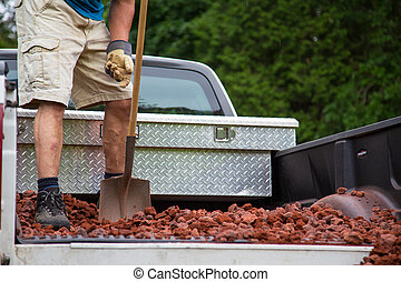 unloading lava stone from truck - a man shovels a load of...