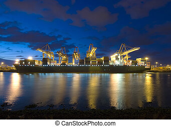 The unloading of a huge bulk carrier during twilight at a large harbor terminal