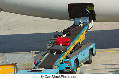 unloading suitcases from plane at the airport