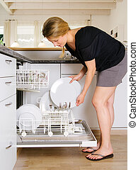 Unloading the dishwasher - Photo of a blond female leaning...