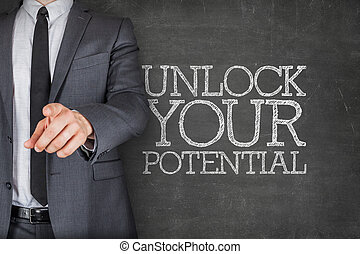 Unlock your potential on blackboard with businessman finger...