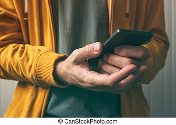 Unlocking smartphone with fingerprint scan sensor, man using...
