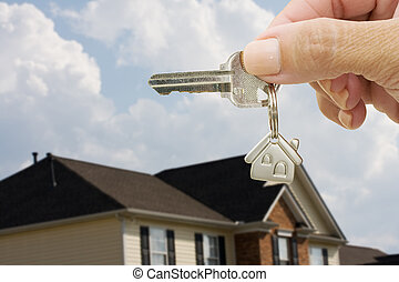 A key on a house keychain in a person�s hand on a house and sky background, unlocking your door