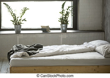 Unmade messy bed in modern bedroom interior with nobody
