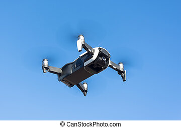 Unmanned drone flies through the air against the blue sky.